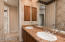 Dual vanity with granite counter, wood medicine chest, walk -in shower, and easy access to a linen closet in the hallway.