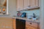 Wet bar with U-line refrigerator and sink and wrap around counter