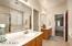 reverse angle on vanity area with door to water closet in between vanities