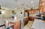 Kitchen with upgraded stainless steel appliances, gas range, DW with hidden buttons, cherry glazed cabinets, pendant lighting, quartz counters.