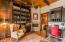 Regal library with hand hewn wood beam and copper tile ceiling detail, custom cabinetry, cantera fireplace and hand hewn hickory wood floors
