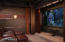 Custom copper doors lead into the sound proof room detailed with wood panel and fashionable material walls with luxurious lounge chairs in front of the built -in projector, projection screen and THX surround sound.