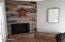 The wood burning fireplace is adorned with 100 year old reclaimed barn wood and custom fireplace doors be an Arcadia artist!