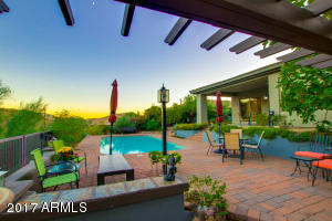 Paved patio surrounds the pool for swimming and viewing the mountains behind the home