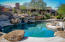 Pool side gourmet kitchen with a diving rock and a variety of water falls and features.