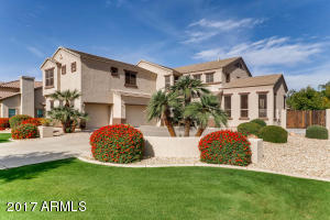 Well manicured lawns and mature landscaping lines the driveway.