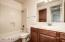 Warm wood vanity, tile flooring and updated fixtures