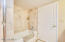 Large private bathroom with separate shower & tub, travertine counter, and ceramic tiled shower.