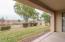 Covered patio overlooks lush yard