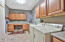 INCREDIBLY LARGE EXPANDED LAUNDRY ROOM WITH BUILT-IN DESK, SINK SOLID SURFACES CHERRY CABINETRY AND EXTRA STORAGE.