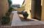 Continuous travertine walkway connects front courtyard to back patio and pool area