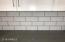 Railroad pattern beveled-edge arctic white tile with charcoal grout