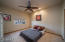 Guest bedroom with ceiling fan and lush carpeting