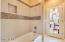 A large hall bath located downstairs with an exterior door to the pool!