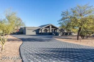 Extensive paver stone driveway gives a grand entrance to this desert hideaway