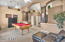 Living room/ dining room with plant shelves, columns, arches, French doors to patio