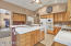 Large kitchen with nearly new refrigerator, breakfast bar, tiled counters, B/I micro, pantry, desk area, hickory cabs