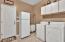 Huge laundry room has cabs, sink , fridge!