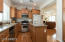 Kitchen features maple cabinets, large center island, gas stove and wood floors.