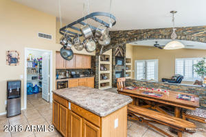 Upgraded kitchen with large pantry, kitchen island, eat in kitchen area and a wine bar (with wine fridge) in the background.
