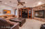 Family room off of the kitchen with a second stone fireplace and wet bar.