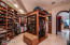 Enormous walk in master closet with custom wood cabinetry and a dressing area.