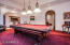 Grand billiard room with custom table lighting and ample space.