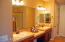 Master bath boasts two medicine cabinets, double sinks, and sunken vanity, as well as walk-in glass shower and closet.