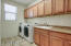 Large laundry room with tons of cabinets and sink!
