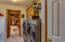 Hallway to the large laundry room with sink and storage