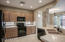 Kitchen features travertine counters, black appliances, smooth top range!