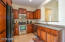 Kitchen area features plenty of cherry wood cabinets and stainless steel appliances.