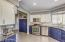 Kitchen with two tone cabinets, granite countertops, and backsplash