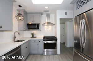 Interior Designed Kitchen with upgrades cabinets and wine rack and Arteriors lighting