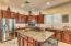 Large open kitchen with granite counters, stainless steel appliances and oversized island.