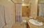 Travertine tile walls and soaking tub with updated fixtures, dual flush toilet