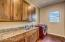 """Large laundry room with 42"""" cabinets, granite countertops and sink. Washer & dryer included."""
