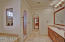 Details in stone carry through to the Master Bath with separate dual sinks, tub, shower, water closet, and full-length vanity mirror