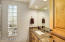 Ensuite bathroom features marble counters and travertine shower/tub surround.