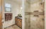 Casita bath offers a walk-in shower with travertine and decorative stone accents and single vanity.