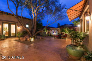 Large private front entry courtyard features a specimen Ironwood tree and Mexican Talavera tile fountain. Double french doors from all bedrooms and den open up to the private courtyard.