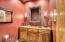 Powder room has a beautiful furniture style vanity.