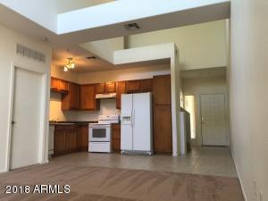 Open kitchen with plenty of room to move around, clean white appliances, and easy flow into living/dining area