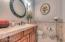 Powder room off of the family room with travertine tile counters and decorative travertine accents on walls!