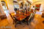 formal dine area has distressed wood beam /Pella brand - French Doors /travertine flooring/ lighting is a gorgeous iron chandelier