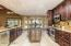 New cabinetry with stunning furniture-like rough edge granite island