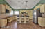 Cream colored cabinets, tiled back-splash, stainless steel appliances, large island, oil rubbed bronze fixtures