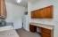 Massive laundry room with sink, fridge, and desk or folding area.