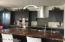 Contemporary costume built kitchen cabinets, wine racks and wine cooler, Large size upscale counter top, one large sink, built in trash cabinet.