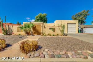 Desert landscaping leads you to an inviting front courtyard